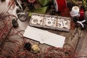 Sada různých dřevěných vánočních hraček pro vánoční strom leží v poli otevřené překližky s vepřem na obálce na dřevěný stůl obklopený stuhy, šňůry, provazy a šišky. Příprava na nový rok.