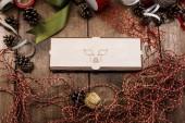 Uzavřené překližky box s nakreslené prase (symbol nadcházející rok) na obálce leží na dřevěný stůl obklopený stuhy, šňůry, provazy a šišky. Příprava na nový rok.