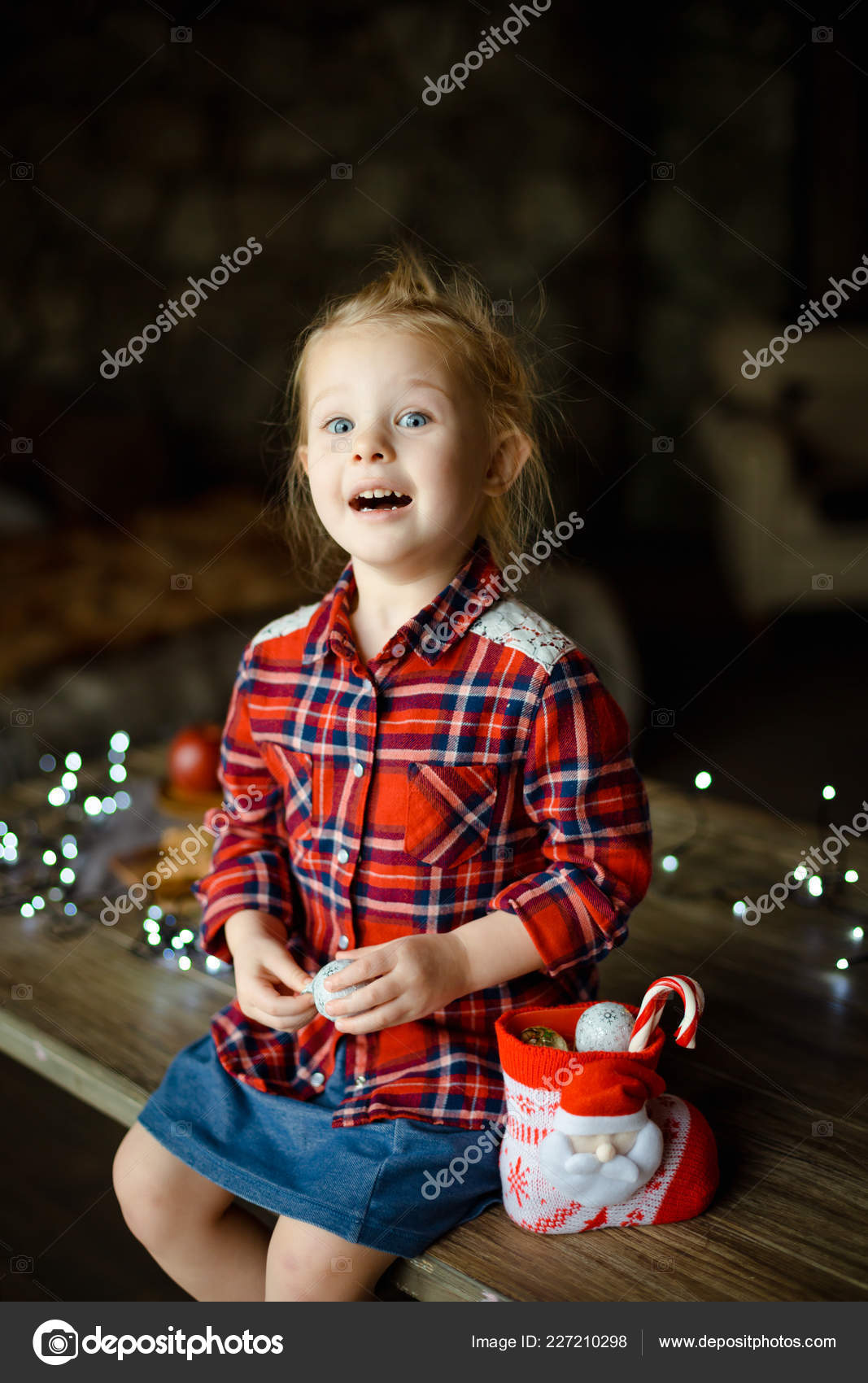 ea5f46852 A beautiful little blonde in a traditional plaid shirt opens a chocolate  bar from her sweet Christmas gift, sitting on a wooden table with a garland  in the ...