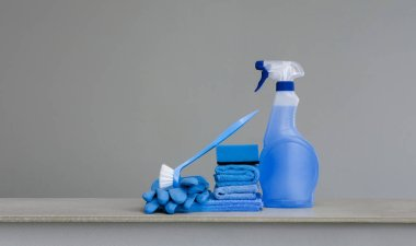 Cleaning blue spray bottle with plastic dispenser, sponge, scrubbing brush for dish, cloth for dust and rubber gloves  on grey background. Cleaning equipment. Copy space.