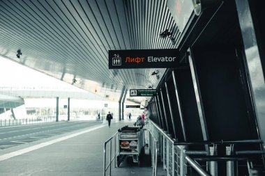 Saint Petersburg, Russian Federation-Aug 16 2018: The exit of the airport Pulkovo in Saint-Petersburg-the building of the airport with a signage and Luggage trolleys and the road along it.