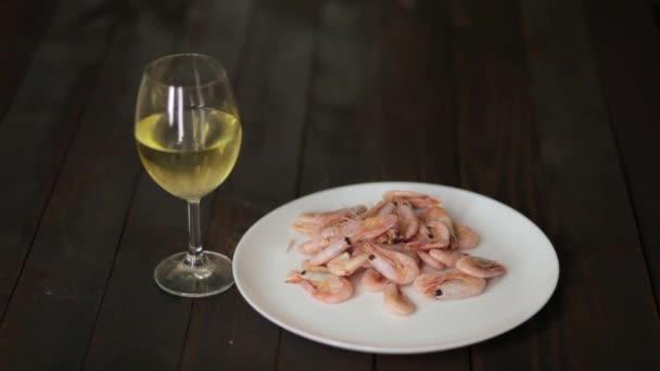 Šťavnaté vařené oceánu krevety na bílé keramické desce se solí a italským kořením