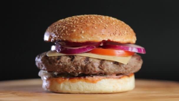 Šťavnatý burger s velký řízek, houska se sýrem, okurka, rajčata, cibuli, zelí, omáčka a sezamová semínka na černém pozadí