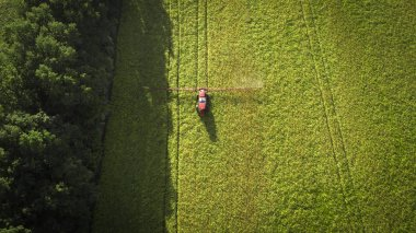 Agricultural machinery in the field. Tractor with a sprayer. Aerial view