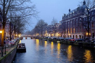 Amsterdam, Netherlands, 02/25/2013, the canals of Amsterdam. The total length of the canal network in the city is about 75 km., there are 165 waterways. They go only small pleasure boats and private boats. More than 1500 bridges of different sizes co