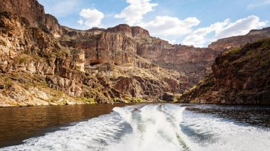 Wake of boat on the water of of Canyon Lake surrounded by red rock mountains in Arizona, USA