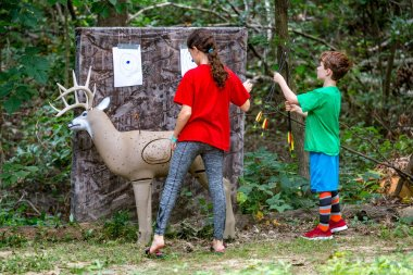 Young brother and sister together in woods practicing bow and arrow archery skills on a model deer target