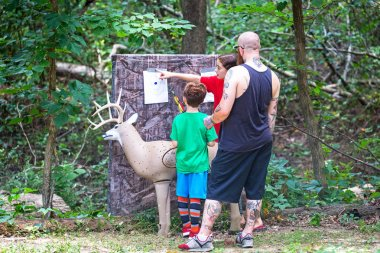 MIDLOTHIAN, VA/USA - JULY 16, 2018:  Father  son and daughter review results of responsible archery target practice with model deer