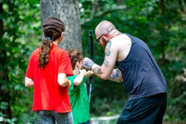 MIDLOTHIAN, VA/USA - JULY 16, 2018: Modern family with father teaching boy and girl to safely shoot a bow with an arrow in the woods