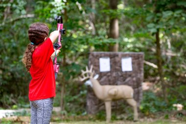 Young pre-teen girl practicing archery skills with bow and arrow at model deer target in the woods