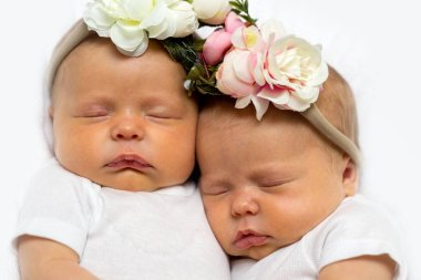 Closeup photo of two identical twin baby girls wearing flower headbands snuggling together while sleeping on white blanket