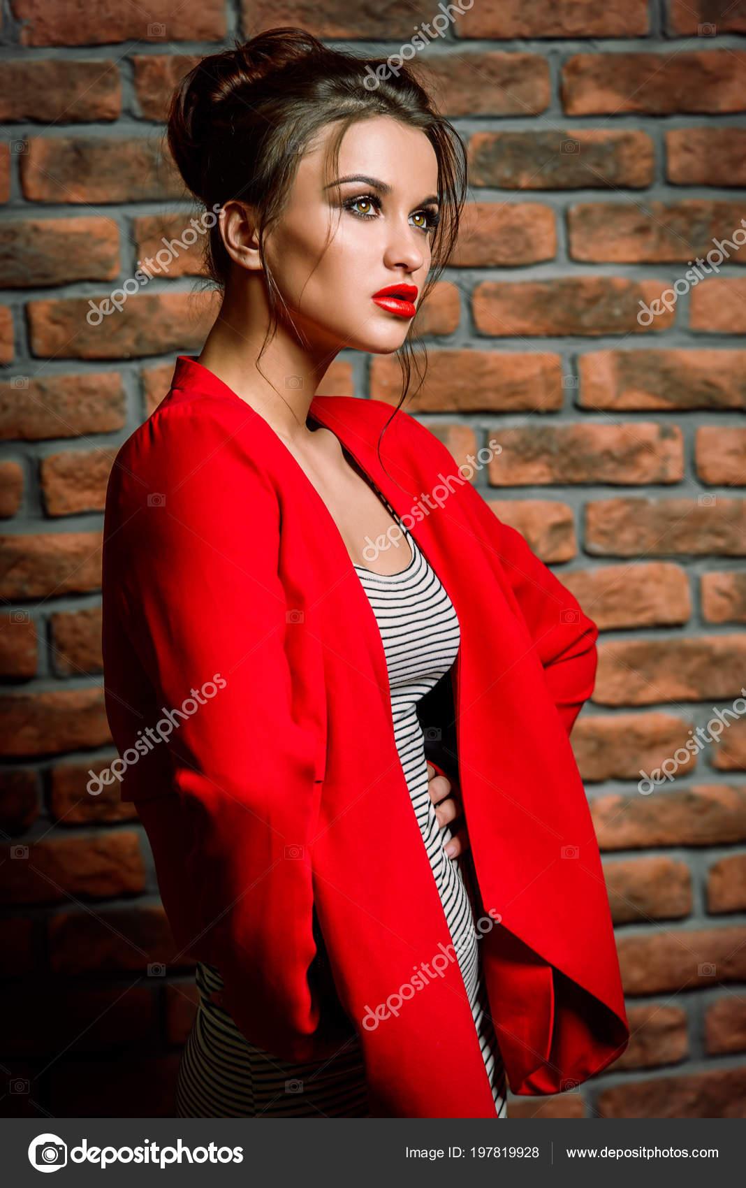 ca1dd817eeda Μόδα πλάνο του μια όμορφη νεαρή γυναίκα σε ριγέ τοποθέτηση φόρεμα και  κόκκινο σακάκι. Studio που γυρίστηκε — Εικόνα από ...