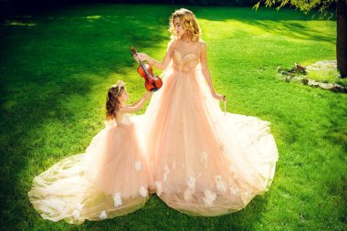 Classical music. Beautiful fairy girl teaches to play the violin a little girl. Musical fairy tales.