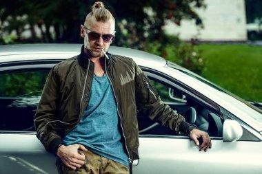 Portrait of a handsome mature man near his car.
