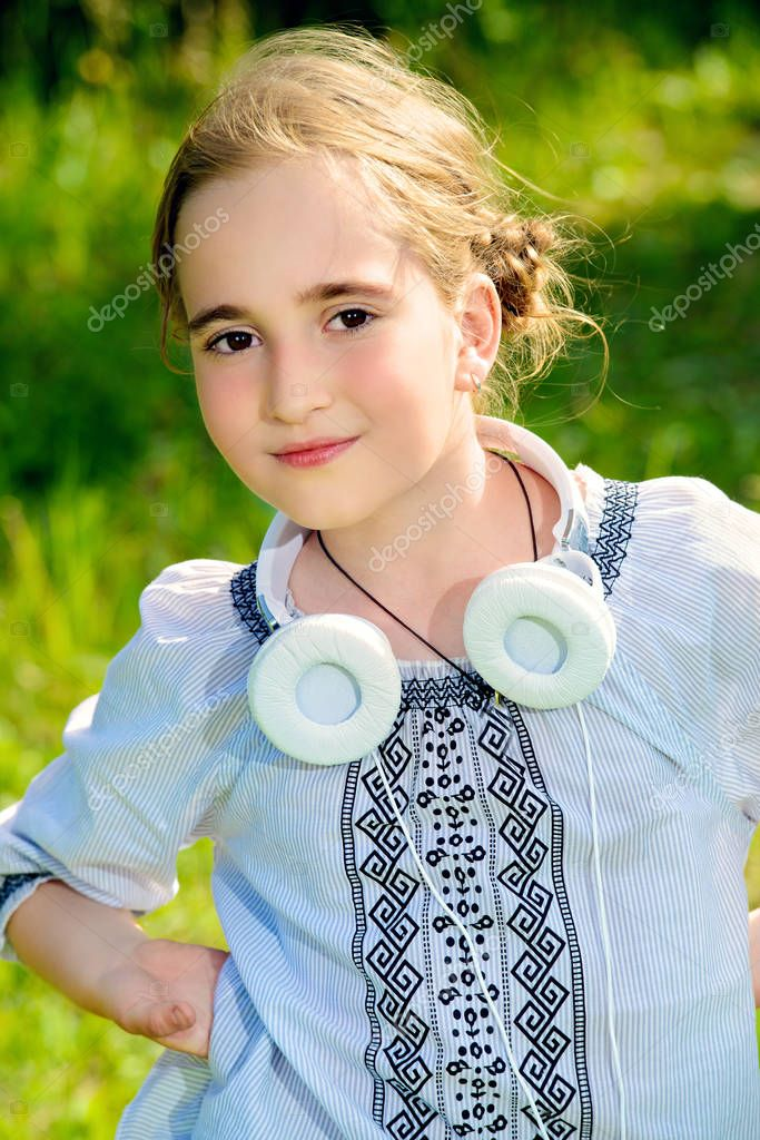 Portrait of a cute girl with headphones in a summer park. Sunny day.