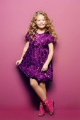 Photo Cute little girl in a beautiful summer dress posing at studio over purple background. Kids fashion.
