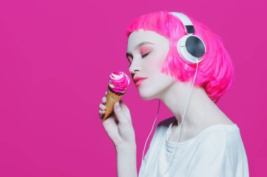 Trendy girl with pink hair wearing headphones is eating ice cream. Pink background. Youth style, leisure.