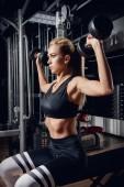 Krásná sportovní žena dělá cvičení s činka v tělocvičně. Zdravý životní styl. Sport, fitness, kulturistika