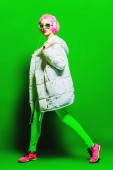 Fotografie In voller Länge Portrait eine trendige Mädchen mit rosa Haaren helle stilvolle Kleidung zu tragen. Grünen Hintergrund. Schönheit, Mode, Jugend-Stil