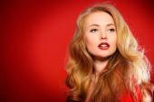Photo Beautiful young woman in red dress and with blonde curled hair. Beauty, fashion. Cosmetics, make-up. Red background.