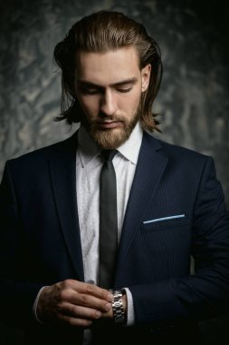 Fashion shot. Handsome young man posing in elegant suit over dark background. Men's beauty, fashion.