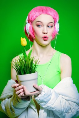 Trendy vivid girl with pink hair wearing headphones holding a flower pot. Green background. Beauty, fashion, youth style.