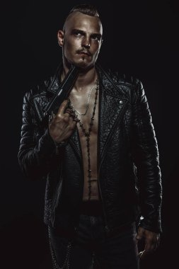 Dark portrait of a serious gangster man with gun wearing black leather jacket.