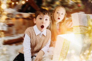 Pretty children sit on the porch of a house decorated for Christmas and open a gift box and surprises. Time for miracles.
