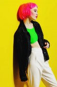 Fotografie Portrait of a trendy girl with pink hair wearing bright stylish clothes. Yellow background. Beauty, fashion, youth style.