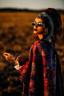 Magnificent fashion woman posing in boho style clothes in the rays of the sunset. Outdoor fashion. Gypsy style.