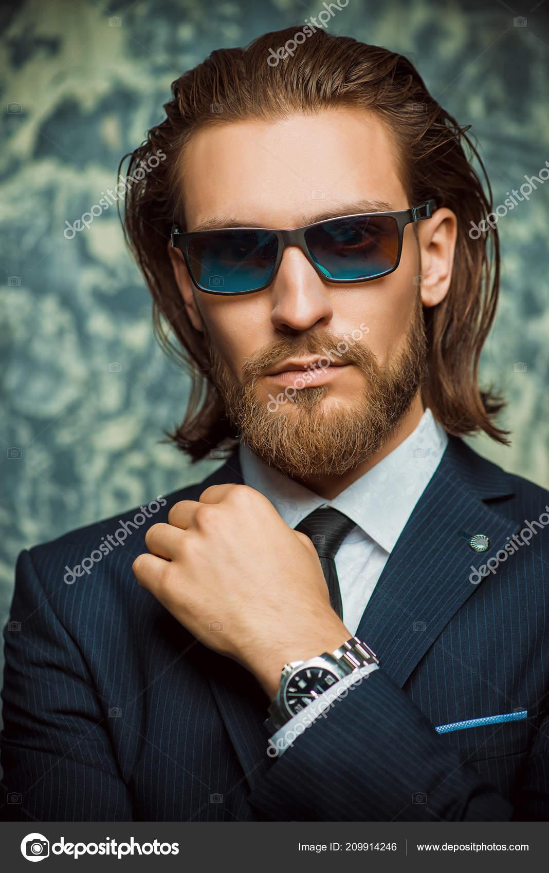 1c15c176fbbccd Hübscher junger Mann posiert in eleganter Anzug und Sonnenbrille auf  dunklem Hintergrund. Männliche Schönheit