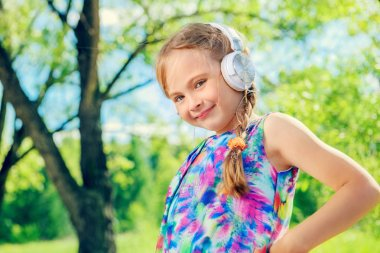 Portrait of a funny girl with headphones in a summer park. Sunny day.