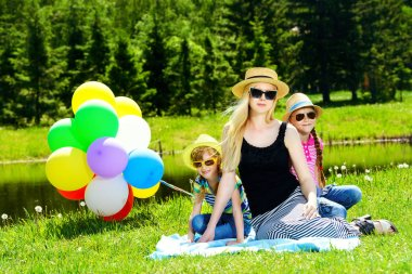 Happy summer day. Cheerful girls resting with their beloved mother in the park. Family concept. stock vector