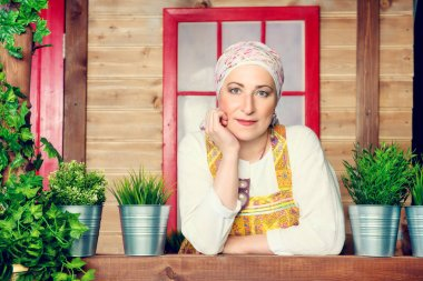 Mature woman in ethnic costume posing on the porch of a wooden house. Portrait. Rural style, decoration.