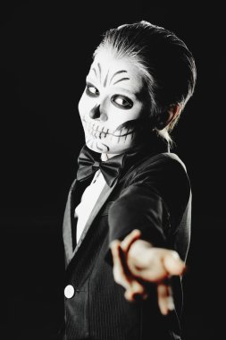 Portrait of a child boy with carnival make-up of a skeleton wearing elegant tail-coat. Studio shot over black background. Halloween. Dia de los muertos. The Day of the Dead.