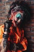 Fotografia Halloween. Ritratto di un uomo sanguinario pagliaccio sopra il muro di mattoni scuri. Pagliaccio maschio zombie. Horror, film thriller