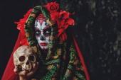 Fotografia Calavera Catrina holding a skull over dark scary background. Sugar skull makeup. Dia de los muertos. Day of The Dead. Halloween.