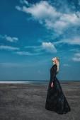 Fotografie Full length portrait of a beautiful gothic woman in long black dress posing outdoor. Beauty, fashion.
