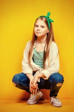 Children's fashion. Beautiful  little girl sitting at studio over yellow background.