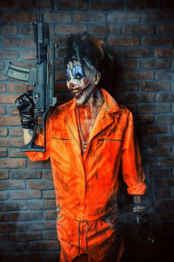 Crazy evil clown man stained in blood is holding a gun. Halloween. Horror, thriller film.