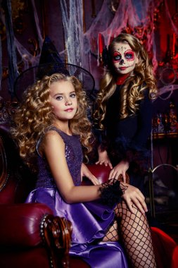 Halloween. Girls in carnival costumes celebrate halloween in the old castle.