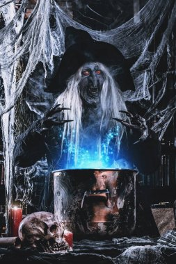 A witch is preparing spell. Halloween costume. Horror movie.