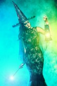A beautiful lady in a costume of witch holding a torch. Halloween. Celebration.