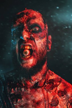 Close up of a creepy scary zombie with an eye in his mouth. Halloween. Horror film.