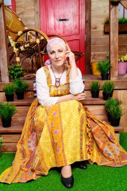 Mature woman in ethnic costume in front of a wooden house. Portrait. Rural style, decoration.