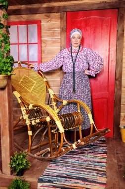 Mature woman in ethnic costume posing on the porch of a wooden house. Full length portrait. Rural style, decoration.