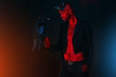 A portrait of a bad demon with a black raven. Horror movie, nightmare. Halloween.