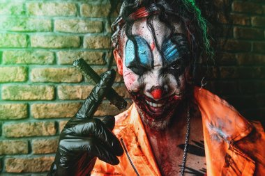 Halloween. Portrait of a disgusting clown man stained in blood over brick wall. Male zombie clown. Horror, thriller film.