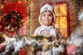 Hübscher Junge steht auf der Veranda eines Hauses dekoriert für Weihnachten mit Geschenk-Box. Zeit für Wunder