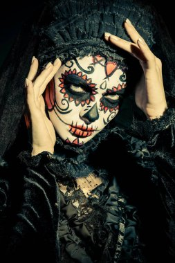 Portrait of Calavera Catrina in darkness. Sugar skull makeup. Dia de los muertos. Day of The Dead. Halloween.